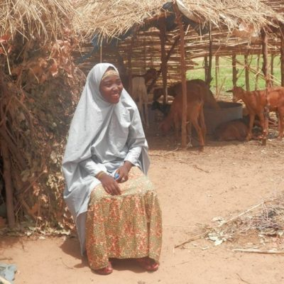Hasana sits proudly in front of the hut she built for herself, amidst the ashes of her old home.